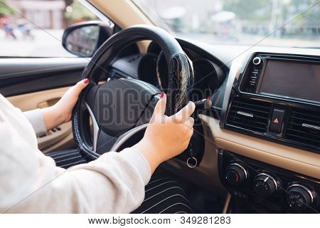 Asian Female Hands On The Steering Wheel Of A Car While Driving With Windshield And Road. Black Woma