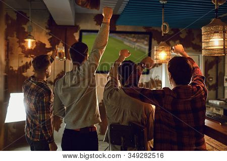 A Group Of Friends Watching Tv Football In A Sports Bar.