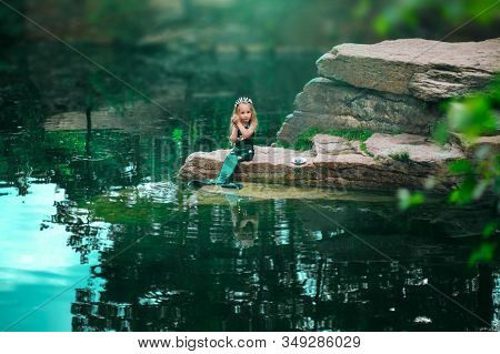 A Little Girl With White Hair With A Mermaid Tail And Shells Is Sitting On The Shore. A Little Merma