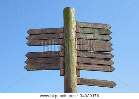 Blank signpost made from weathered wood with 15 arrows against a blue sky