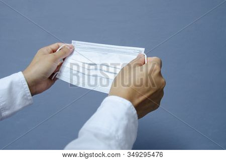 White Surgical Mask  In Hand On Grey Background.protection Corona Virus Concept.