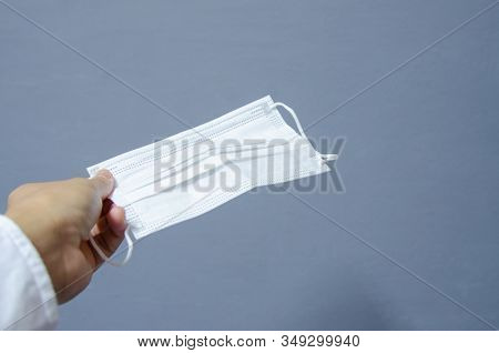 Close Up Hand With Surgical Mask For Protecting Corona Virus On Grey Background.