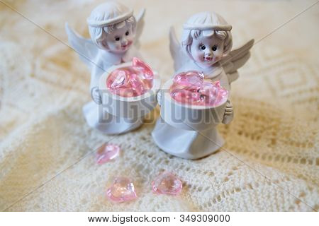 Two White Ceramic Angel Figurines With Baskets With Pink Hearts On A Light Background. Angel Figurin