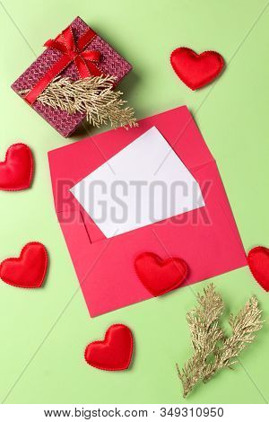 Golden Branch With Card, Gift Box And Hearts On A Green Background. Copy Space. Top View.