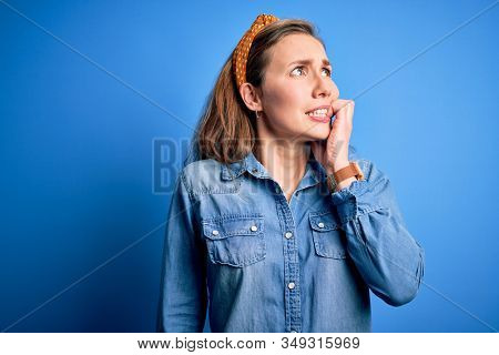 Young beautiful blonde woman wearing casual denim shirt and diadem over blue background looking stressed and nervous with hands on mouth biting nails. Anxiety problem.