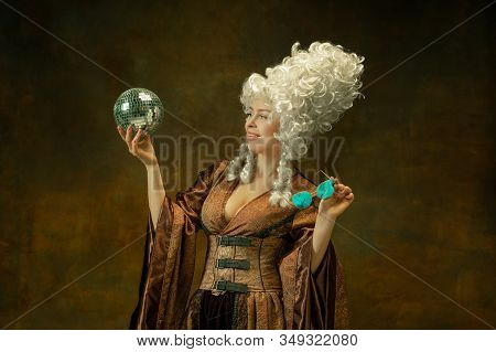 Ready For Party. Portrait Of Medieval Young Woman In Vintage Clothing With Discoball, Eyewear On Dar
