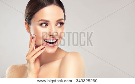Beautiful Young Woman With Clean Fresh Skin Touching Her Face . Girl Facial  Treatment   . Cosmetolo