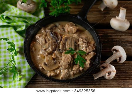 Slow Cooked Pork Stew With Mushrooms In Creamy Sauce Served With Parsley