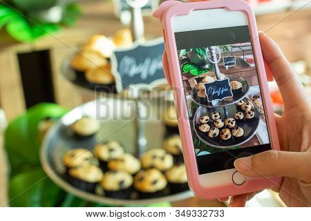 The Cafe Owner Uses A Smartphone To Take Pictures Of Newly Finished Cupcakes To Promote On Online Me