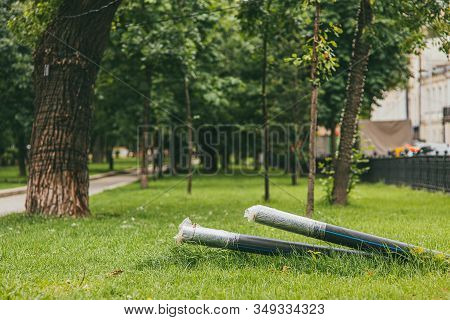 2 Black Cables In Protective Hdpe Tube On A Green Lawn In A Park. Installation Of A Line Of Metal An