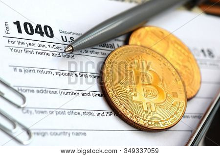 The Pen, Bitcoins And Dollar Bills Is Lies On The Tax Form 1040 U.s. Individual Income Tax Return. T