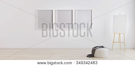 Easel With Canvas In Bright White Room With Three Blank Frames For Mockup. Artist Workspace. Empty B