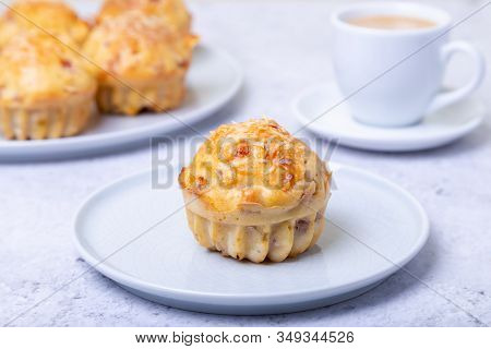 Muffins With Ham And Cheese. Homemade Baking. In The Background Is A Plate With Muffins And A Cup Of