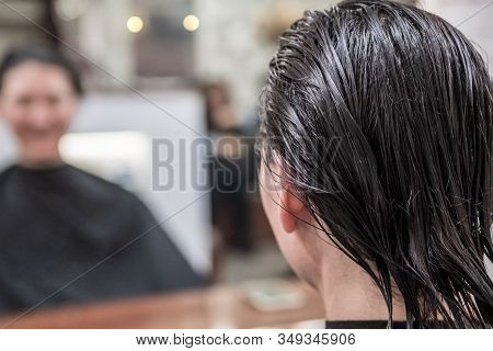 Brunette Woman With Wet Hair Looking Her Reflection In Mirror And Waiting For Haircut In Hairdressin