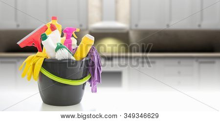 Cleaning Supplies In A Bucket Against Blur Kitchen Cabinets Background.
