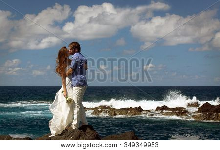 Young Just Married Couple Kissing On Ocean Rock Shore. Side View. Ocean Waves, Splash Of Water And B