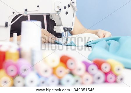 Sewing Studio. Seamstress Sewing On A Sewing Machine Close-up. A Set Of Items For Needlework: Thread