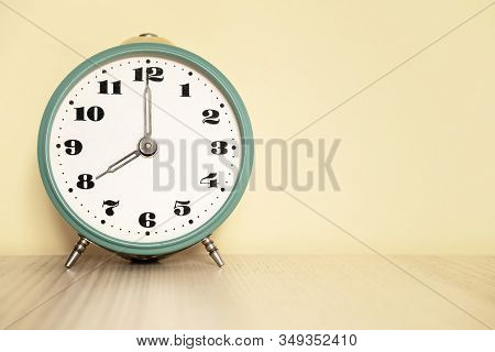 Antique Analog Clock With Hands Set At 08:00. 20:00 The Alarm Clock Is On The Table