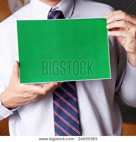 Manager holding empty green sign in front of his chest