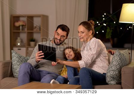 family, people and technology concept - happy smiling father, mother and little daughter with tablet pc computer at home at night