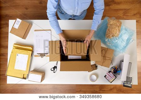 delivery, mail service, people and shipment concept - close up of woman packing fragile parcel boxes at post office