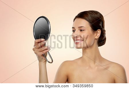 beauty, bodycare and people concept - beautiful young woman with bare shoulders looking to mirror over beige background poster