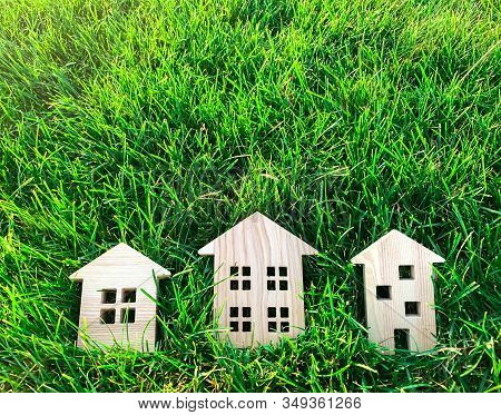 Miniature Wooden Houses On Green Grass. Real Estate Concept. Modern Housing. Eco-friendly And Energy