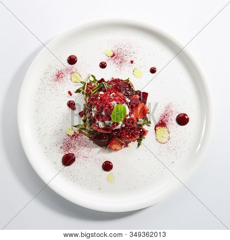 Baked beet salad with citrus fruits and stracciatella on restaurant plate isolated. Red salat with sliced beets, grapefruit, pomegranate, cheese ice cream topview
