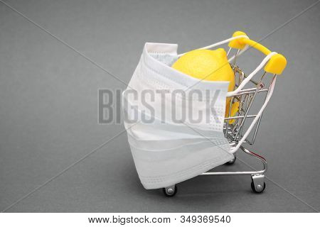 A Medical Mask Is Placed On A Shopping Cart Containing A Fresh Lemon. Medicine And Healthcare. Prote