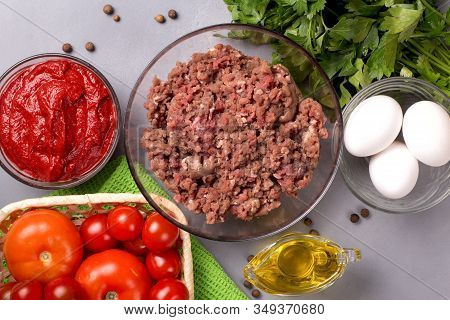 Minced Meat With Tomatoes, Eggs, Parsley And Pepper On A Gray Background. Forcemeat. Top View.