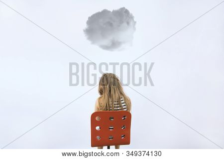 Girl Sitting On Red Chair Under Dark Cloud. Mental Health Concept. Teenager In Depression. Kid At Re