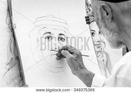 Al Dhafrah, Uae - January 12, 2019: Painting A Portrait, Creating Art, Hand In Frame