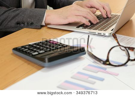 Blurred Selective Focus, Smart Businessman With Suit Calculate And Type On Financial, Tax And Busine