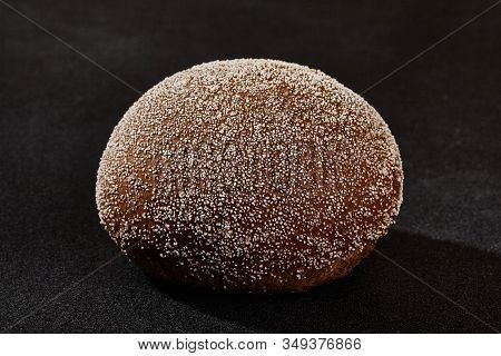 Fresh, Palatable Baked Bun Sprinkled With Ground Coconut Against Black Background With Copy Space. R