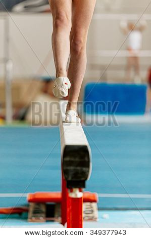Girl Gymnast Point Your Toes On Balance Beam In Gymnastics Competition