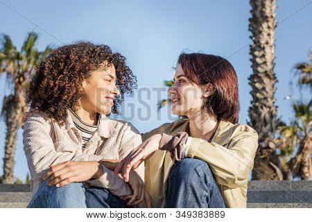 Young Interracial Couple Of Homosexual Women Talking Sitting On The Stairs, Concept Of Sexual Freedo