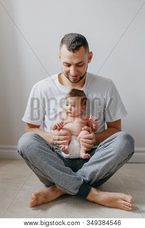 Happy Caucasian Father Holding Newborn Baby On Laps Knees. Man Parent Embracing Rocking Child Daught