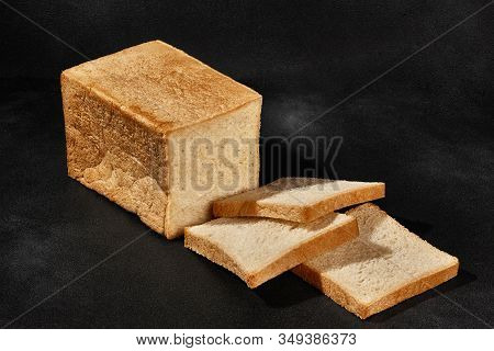 Sliced Loaf Of Fresh, Palatable Baked White Bread Against Black Background With Copy Space. Close-up