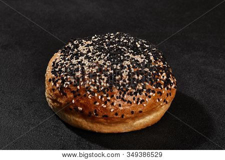 Fresh, Palatable Baked Bun Sprinkled With Sesame Seeds Against Black Background With Copy Space. Rur