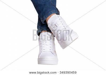 Women Legs In Jeans And Sneakers. Woman Legs In Blue Denim Pants Wearing Modern White Sneaker. Fashi