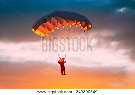 Skydiver On Parachute In Sunny Sunset Sky. Active Extremal Hobbies. Parachutist Paratrooper In Color