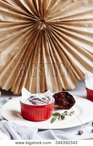 Chocolate Muffins In Red Cups. Small Glazed Ceramic Ramekin With Brown Cakes On A Gray And White Bac