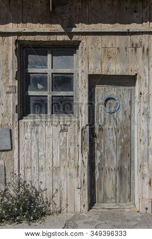 Old Wooden Door With Porthole Window And A Window Of A Warehouse Or Barn, Wood Texture Or Background