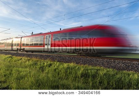 Modern Red Train, In Motion Blur, Traveling Through Green Nature, German Countryside, On Summer Sunn
