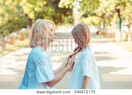 Woman Mother Smiling Looking At Talking To Her Upset Little Daughter Girl Holding Her Blond Hair Tre