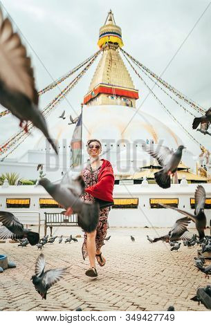 Beautiful Female Sincerely Smiling And Going By Square Through Pigeons Flock With Boudhanath Stupa -