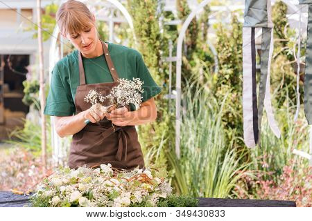 Gardener woman creating grave decoration in her shop