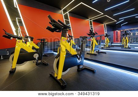 Modern spinning class, gym with indoor bikes in a row