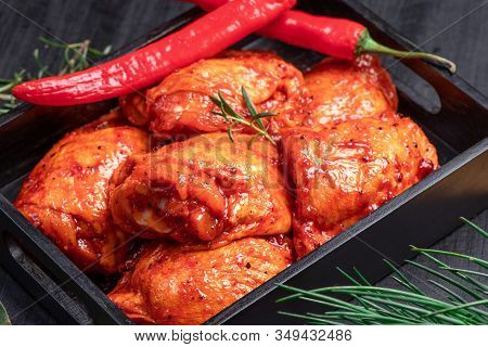 Raw Chicken Quilted In Red, Tomato Marinade On A Black Plate And Spices.raw Meat In The Marinade.. D