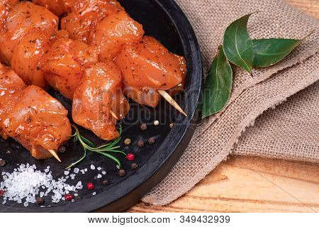 Raw Marinated And Spicy Chicken Skewers.raw Chicken Skewers In Marinade With Spices On A Black Plate